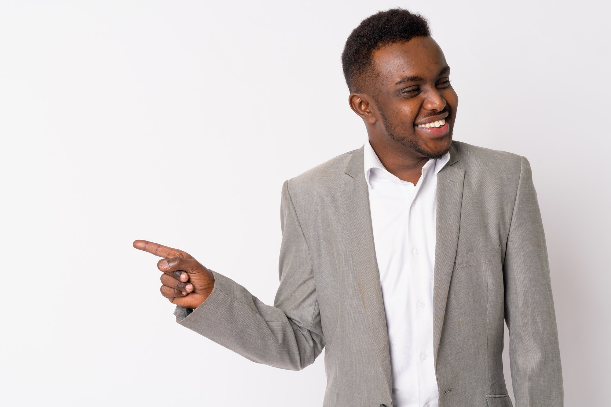 Portrait of happy young African businessman laughing and pointing finger